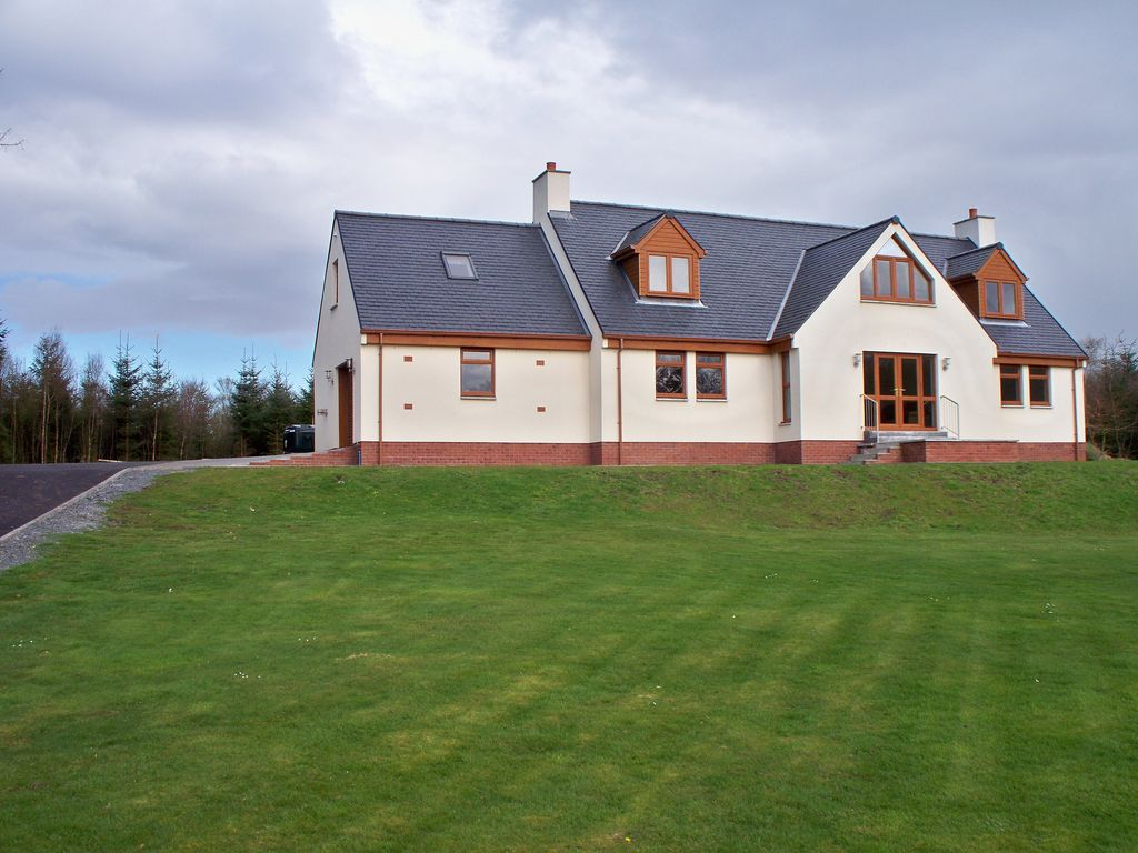 A large two story house sits at the top of an empty lawn with a clouded blue sky and woods in the background.